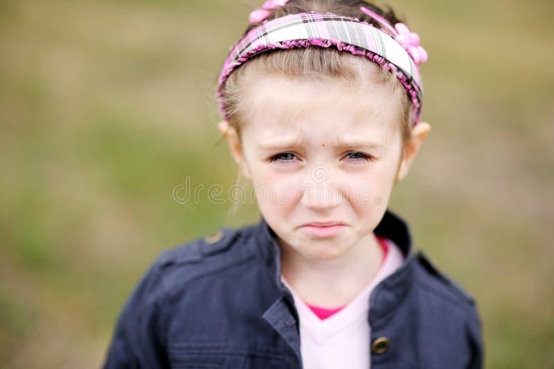Het leuke kindmeisje maakt verstoord weepy gezicht royalty-vrije stock afbeelding