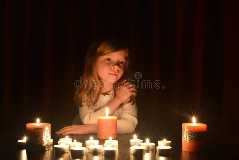 Het leuke kleine blondemeisje houdt haar hand op haar schouder en zij bekijkt de brandende kaars Veel kaarsen zijn rond h stock foto