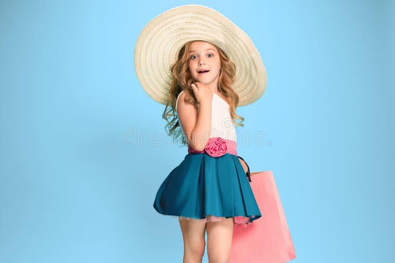 Het leuke kleine Kaukasische donkerbruine meisje in kledingsholding het winkelen zakken royalty-vrije stock fotografie