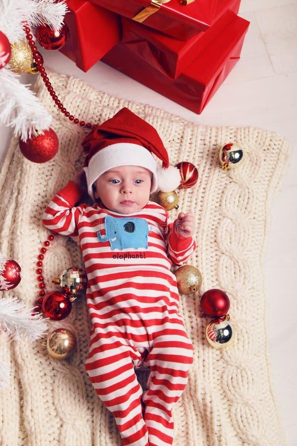Het leuke kleine Kerstmanbaby stellen naast Kerstboom bij comfortabel huis met Nieuwjaardecoratie royalty-vrije stock foto