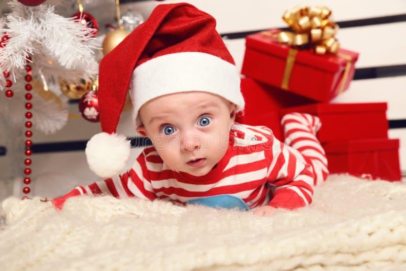Het leuke kleine Kerstmanbaby stellen naast Kerstboom bij comfortabel huis met Nieuwjaardecoratie stock fotografie