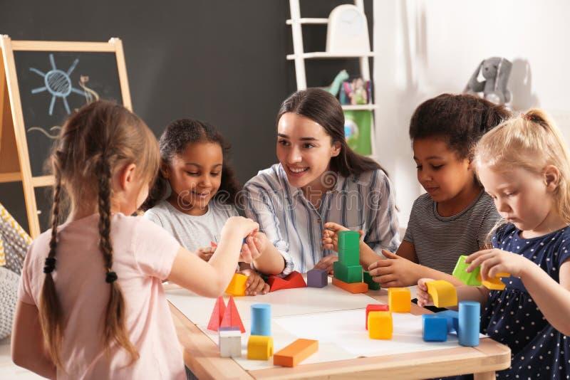 Het leuke kleine kinderen en van de kinderdagverblijfleraar spelen met bouwstenen in kleuterschool stock foto's