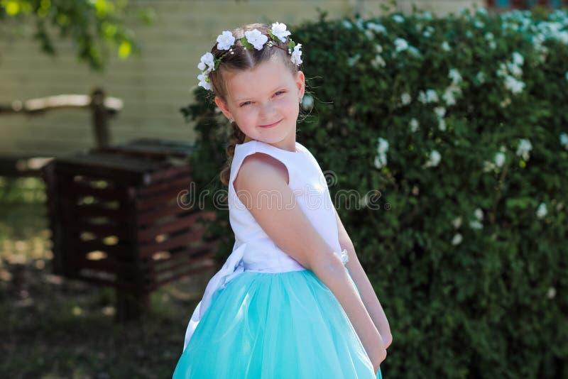 Het leuke kleine meisje kleedde zich in blauwe en witte kleding met een kroon van kunstbloemen op haar hoofd, kind in een feestel stock fotografie