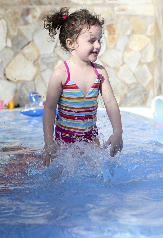 Het leuke kleine meisje speelt in het zwembad royalty-vrije stock afbeeldingen