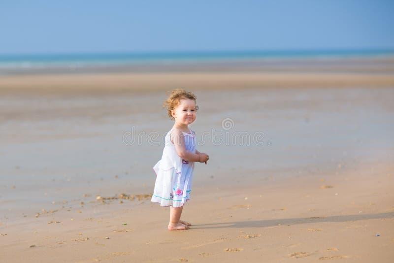 Het leuke krullende babymeisje spelen op een mooi tropisch strand royalty-vrije stock afbeeldingen