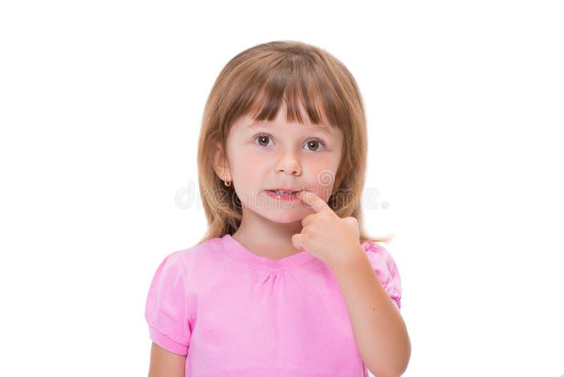 Het leuke meisje 3 éénjarigen in roze t-shirt houdt vingers in mond of bijt spijkers die op witte achtergrond worden geïsoleerd S royalty-vrije stock foto