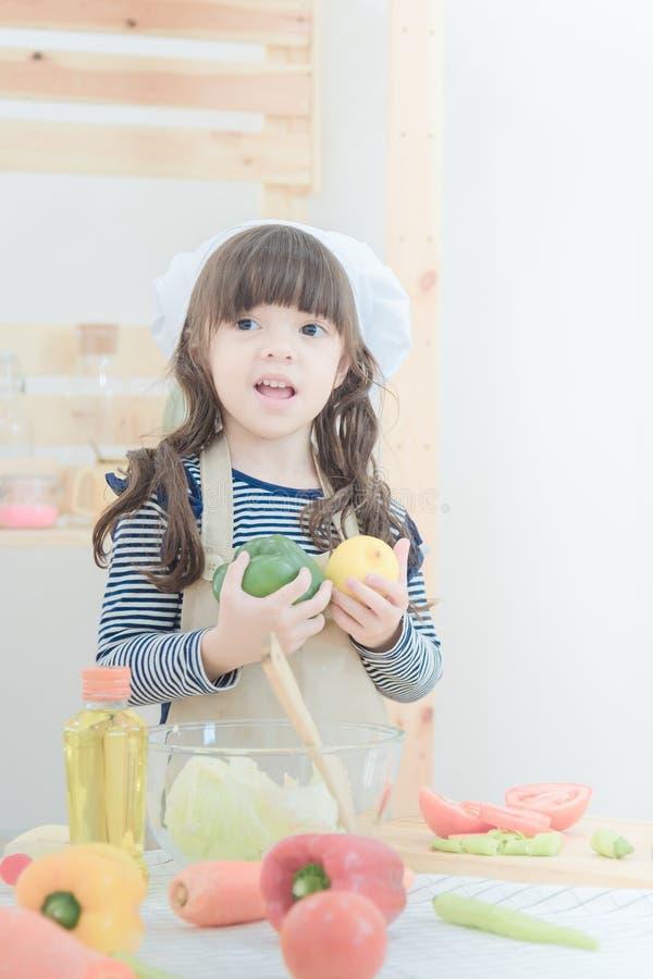 Het leuke meisje bereidt gezonde voedselsalade in keukenruimte voor Foto desig royalty-vrije stock foto's