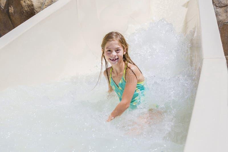 Het leuke meisje berijden onderaan een waterdia bij een waterpark royalty-vrije stock foto's