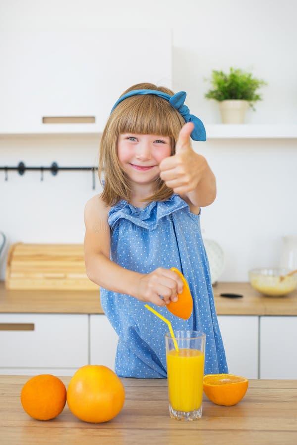 Het leuke meisje in blauwe kleding drukt een sinaasappel en toont als royalty-vrije stock foto's