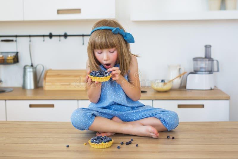 Het leuke meisje in blauwe kleding eet cakes op een lijst stock fotografie