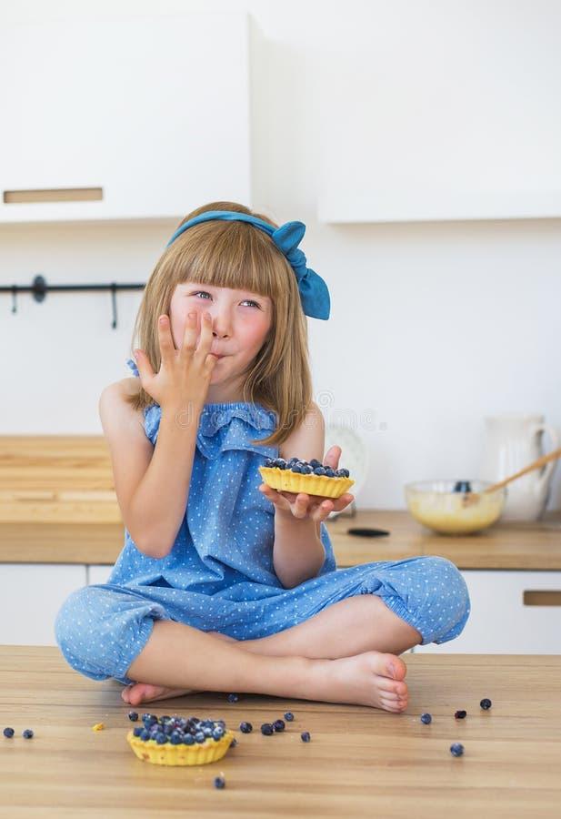 Het leuke meisje in blauwe kleding eet een cake en likt haar vingers royalty-vrije stock foto's