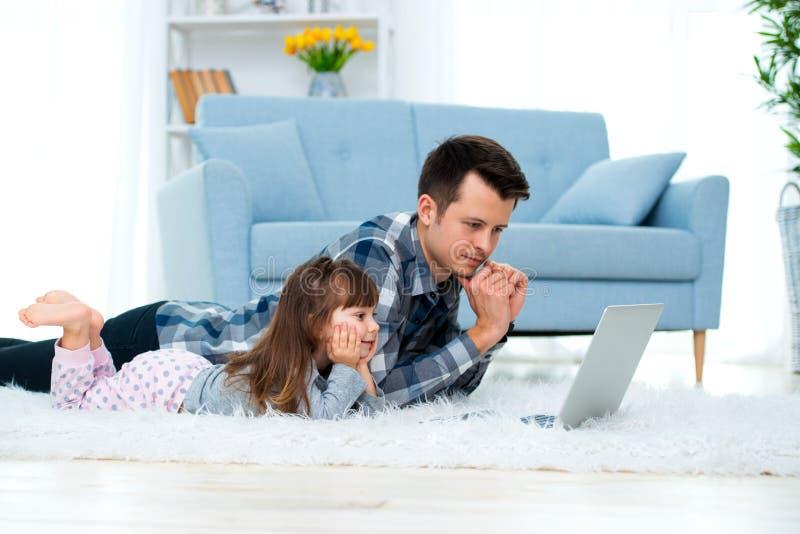 Het leuke meisje, de dochter, de zuster en de jonge de papavader of broer bekijken de laptop monitorcomputer, liggend op tapijt o stock foto