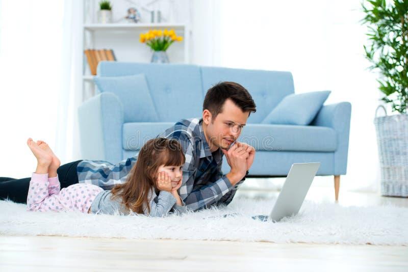 Het leuke meisje, de dochter, de zuster en de jonge de papavader of broer bekijken de laptop monitorcomputer, liggend op tapijt o royalty-vrije stock afbeelding