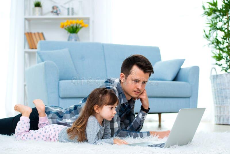 Het leuke meisje, de dochter, de zuster en de jonge de papavader of broer bekijken de laptop monitorcomputer, liggend op tapijt o stock afbeelding