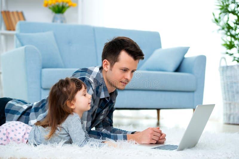 Het leuke meisje, de dochter, de zuster en de jonge de papavader of broer bekijken de laptop monitorcomputer, liggend op tapijt o royalty-vrije stock foto's