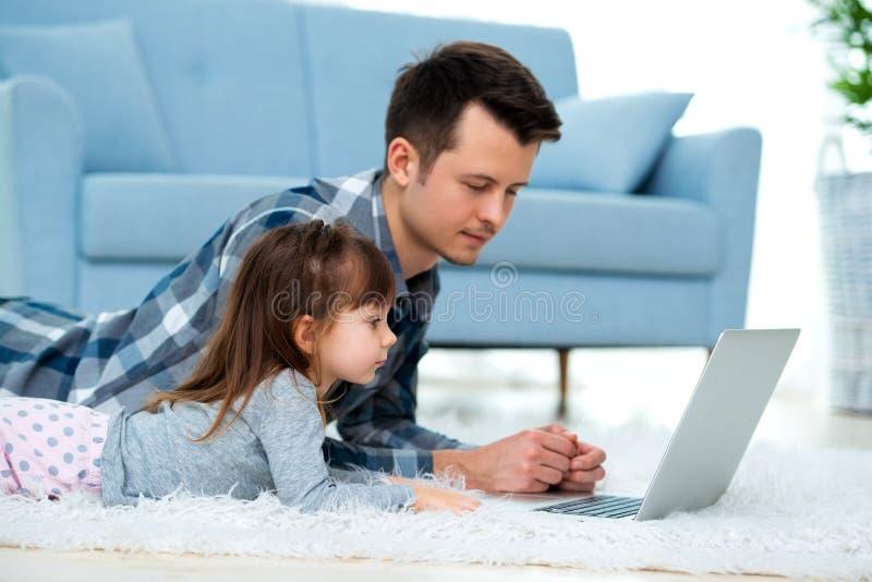 Het leuke meisje, de dochter, de zuster en de jonge de papavader of broer bekijken de laptop monitorcomputer, liggend op tapijt o stock fotografie