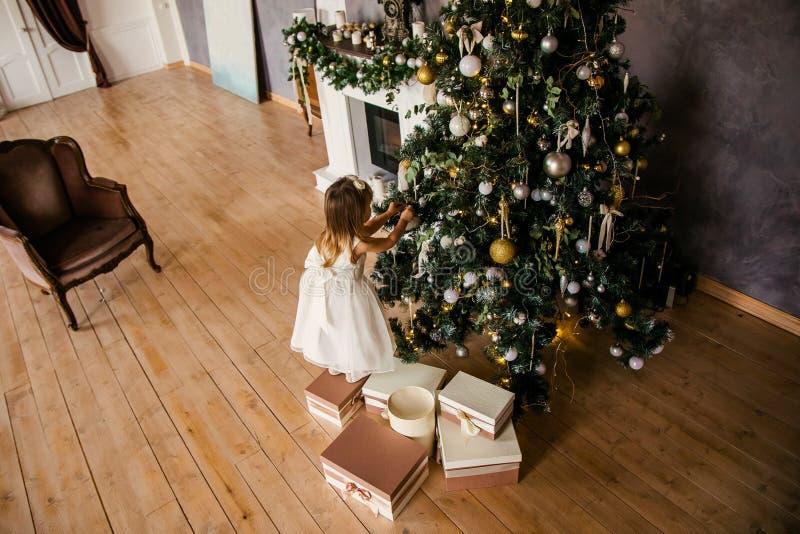 Het leuke meisje in de witte kleding met groot stelt dichtbij de Kerstboom voor stock foto