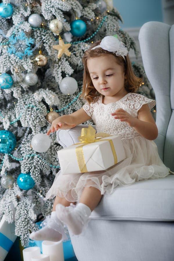 Het leuke meisje in de zitting van de bklomkleding als voorzitter en opent doos met heden voor achtergrondkerstboomblauw royalty-vrije stock afbeelding