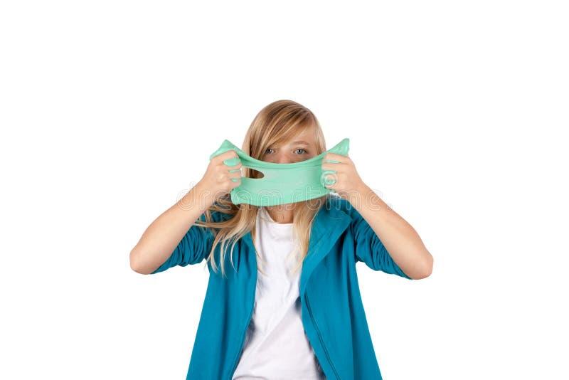 Het leuke meisje die groen slijm houden kijkt als gunk voor haar gezicht stock afbeeldingen