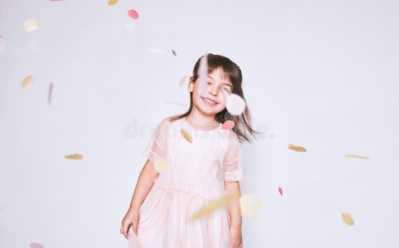 Het leuke meisje die roze kleding in Tulle met prinseskroon dragen die op confettien dansen verrast op witte studiomuur stock afbeelding