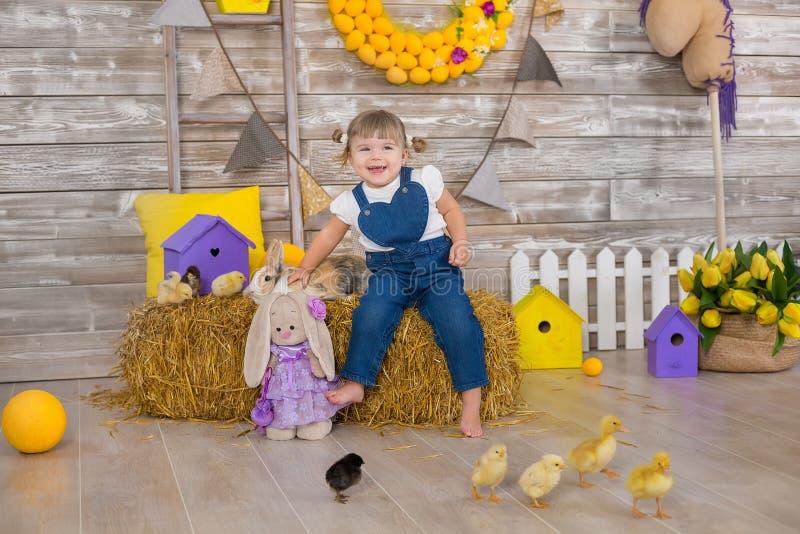 Het leuke meisje die rustieke jeans dragen die huid spelen - en - zoekt met een kippenzitting bij een hooiberg Het concept kinder royalty-vrije stock afbeeldingen