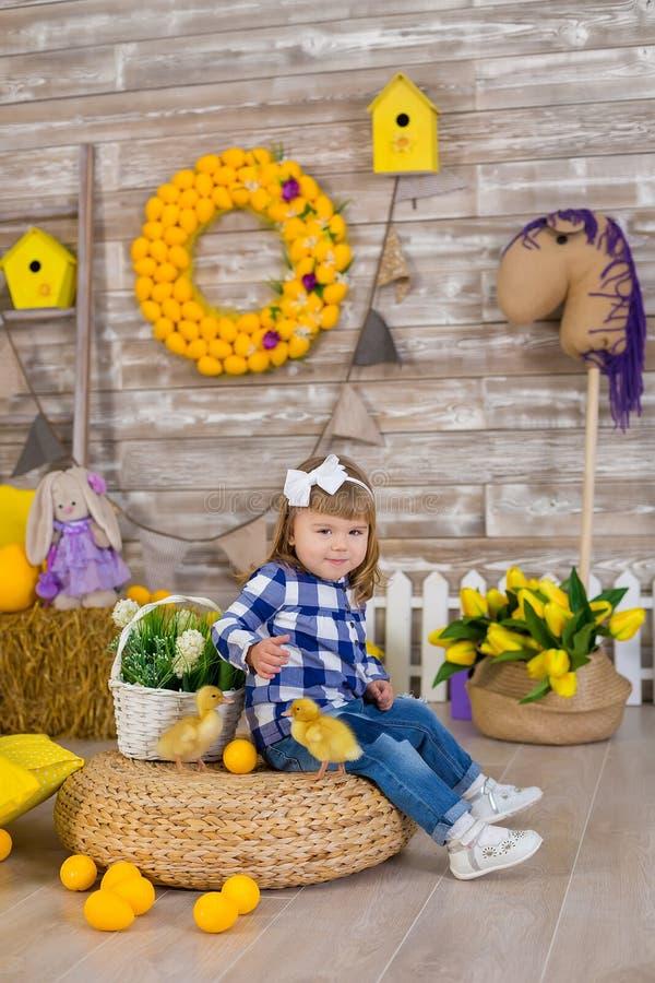 Het leuke meisje die rustieke jeans dragen die huid spelen - en - zoekt met een kippenzitting bij een hooiberg Het concept kinder stock fotografie