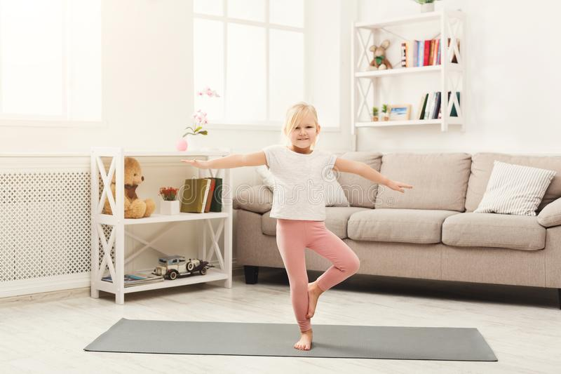 Het leuke meisje die yoga doen oefent thuis uit royalty-vrije stock foto's