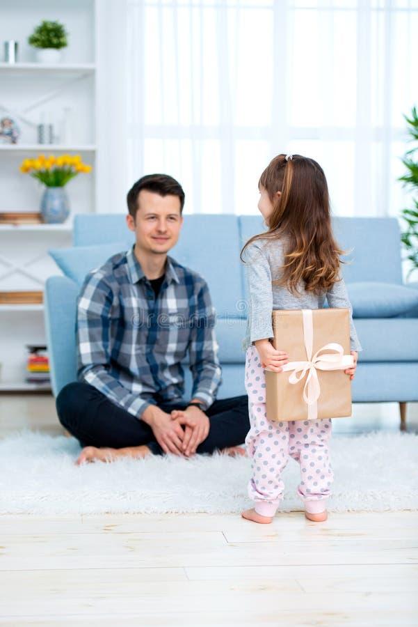 Het leuke meisje, dochter, zuster geeft een giftdoos aan jonge papavader of broer Allebei glimlachen Vaderdagvakantie concep royalty-vrije stock foto's