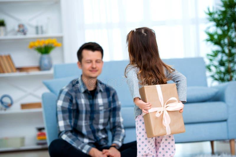 Het leuke meisje, dochter, zuster geeft een giftdoos aan jonge papavader of broer Allebei glimlachen Vaderdagvakantie concep stock afbeeldingen
