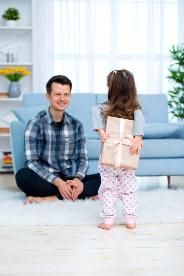 Het leuke meisje, dochter, zuster geeft een giftdoos aan jonge papavader of broer Allebei glimlachen Vaderdagvakantie concep royalty-vrije stock foto