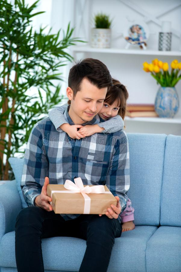 Het leuke meisje, dochter, zuster koestert vader of broer en geeft hem een gift stock foto's