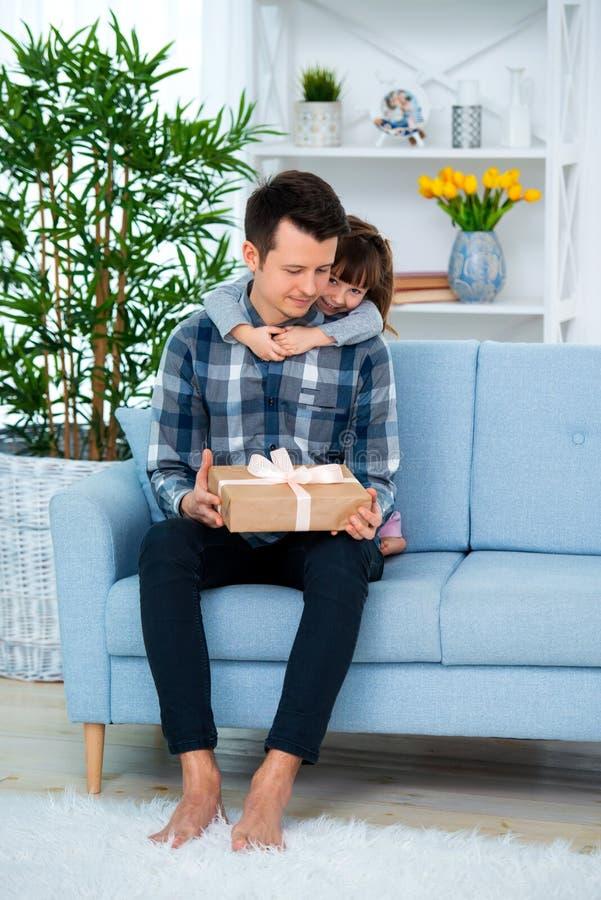 Het leuke meisje, dochter, zuster koestert vader of broer en geeft hem een gift stock afbeeldingen