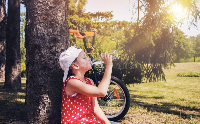 Het leuke meisje drinkt water van een plastic fles stock foto