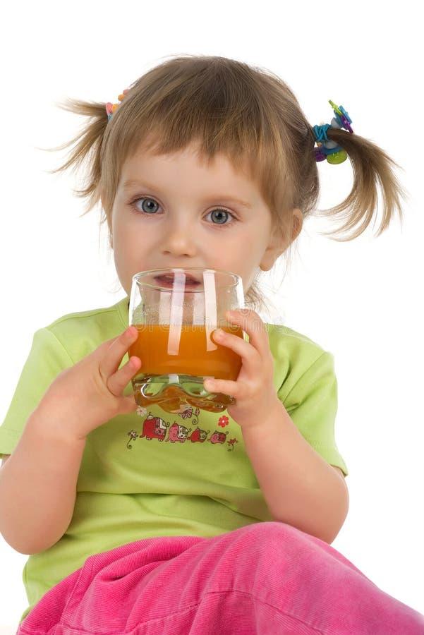 Het leuke meisje drinkt wortelsap stock foto's