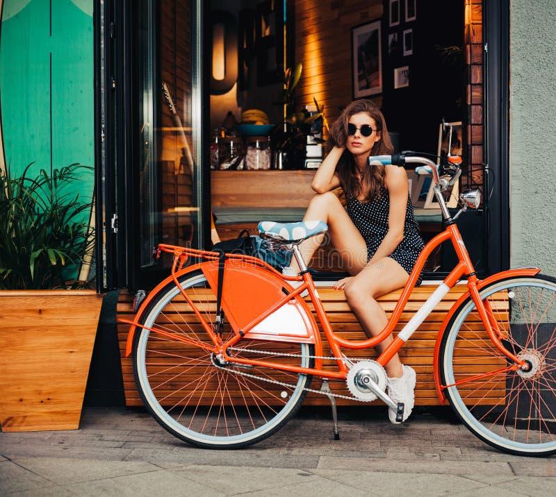 Het leuke meisje in een de zomerkleding zit met rode uitstekende fiets in een Europese stad De zonnige zomer Het meisje in een go royalty-vrije stock fotografie
