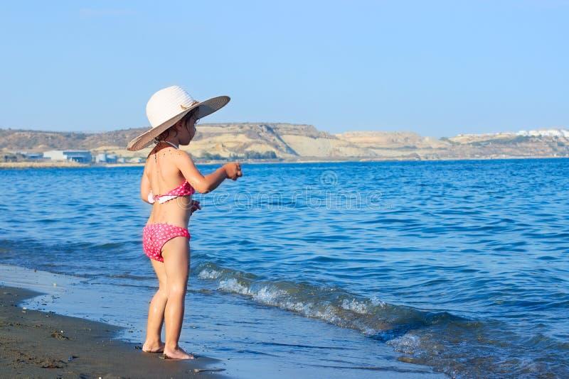 Het leuke Meisje in een grote hoed speelt de nevel van golven bij stock afbeelding