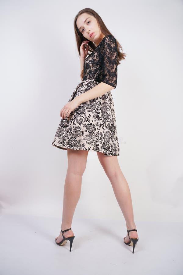 Het leuke meisje in een kantkleding bevindt zich op een witte achtergrond in de Studio royalty-vrije stock afbeeldingen