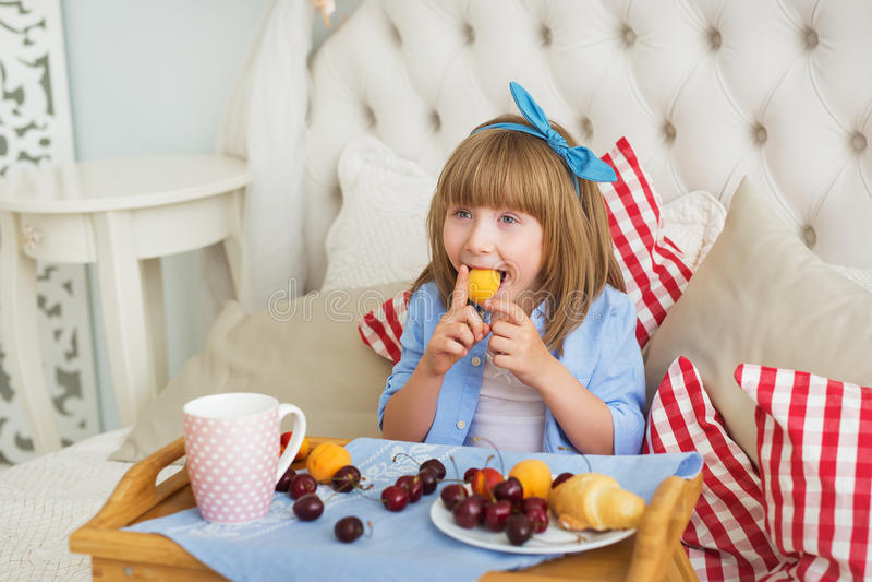 Het leuke meisje eet grappig op een bed in de ochtend royalty-vrije stock afbeeldingen