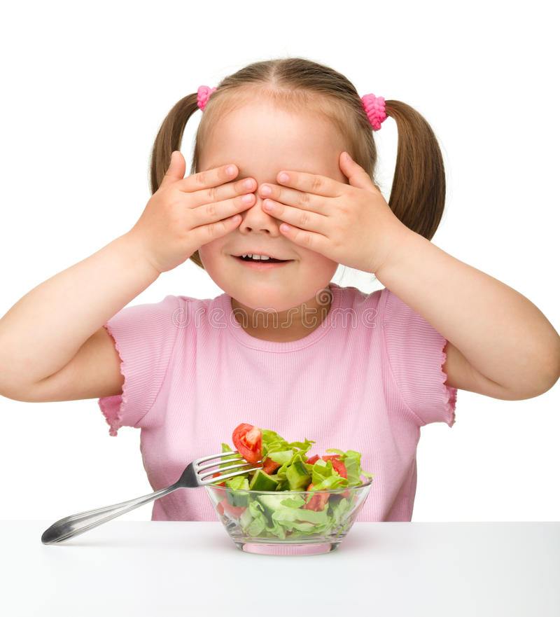Het leuke meisje eet plantaardige salade royalty-vrije stock afbeeldingen