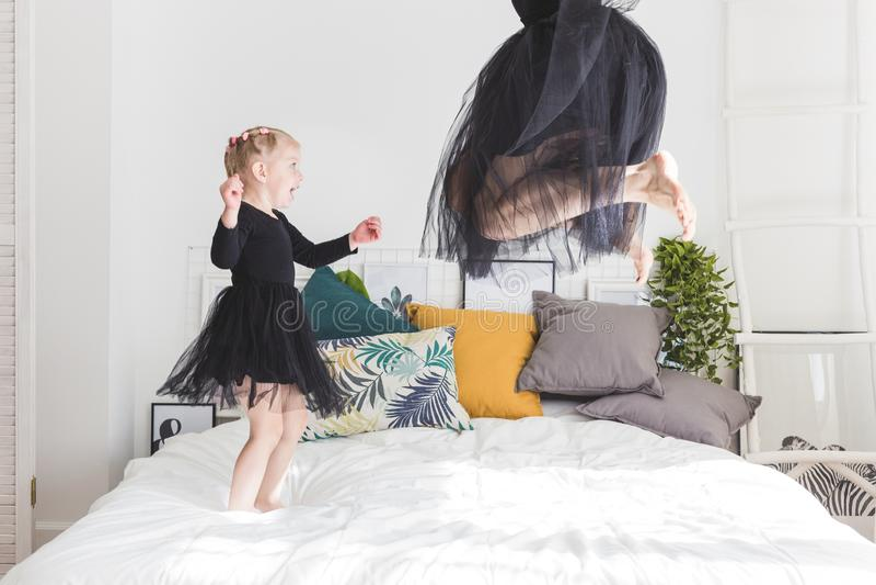 Het leuke meisje en haar mamma hebben pret thuis op het bed stock afbeelding
