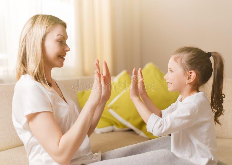Het leuke meisje en haar mooie moeder zijn thuis speelspelen, samen slaand handen stock foto