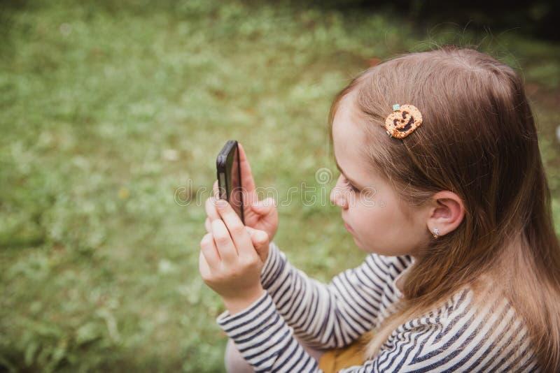 Het leuke meisje gebruikt de slimme telefoon Gras op achtergrond Op meisje een haarspeld met een pompoen stock fotografie