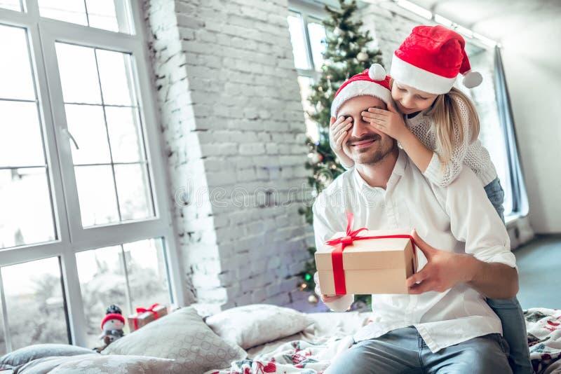 Het leuke meisje geeft haar knappe vader een giftdoos stock foto's