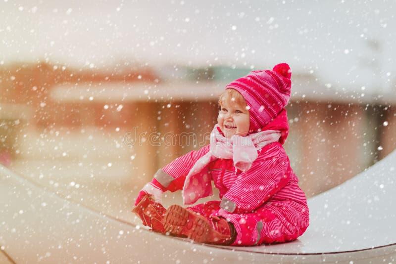 Het leuke meisje geniet van eerste sneeuw in de stad, de winterpret stock fotografie