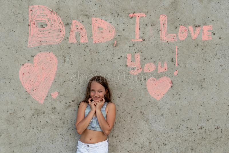 Het leuke meisje glimlachen op de achtergrond van de muur met woordenpapa I houdt van u Concept gelukkige vaderdag royalty-vrije stock afbeeldingen