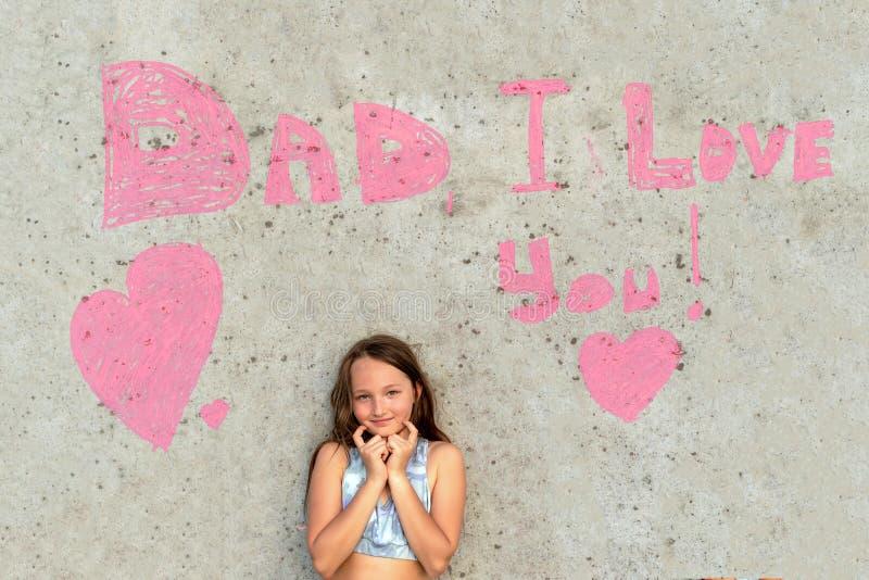 Het leuke meisje glimlachen op de achtergrond van de muur met woordenpapa I houdt van u Concept gelukkige vaderdag stock afbeelding