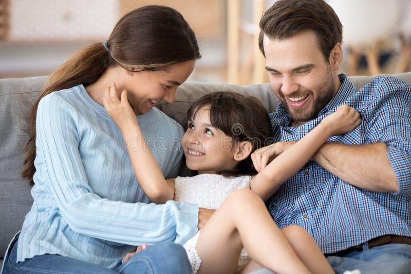 Het leuke meisje heeft pret het ontspannen thuis met ouders stock afbeelding