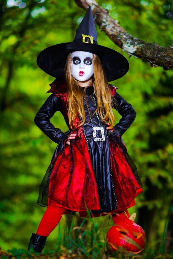 Het leuke meisje kleedde zich aan Halloween-kostuum in donker bos stock afbeelding