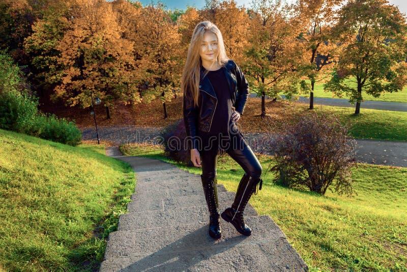 Het leuke meisje kleedde zich in laag en laarzen zittend op de herfstachtergrond royalty-vrije stock afbeeldingen