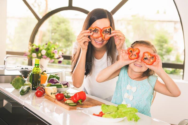 Het leuke meisje koken met haar moeder stock foto's